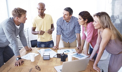 Co-workers gather around a laptop to do research and implement new ideas